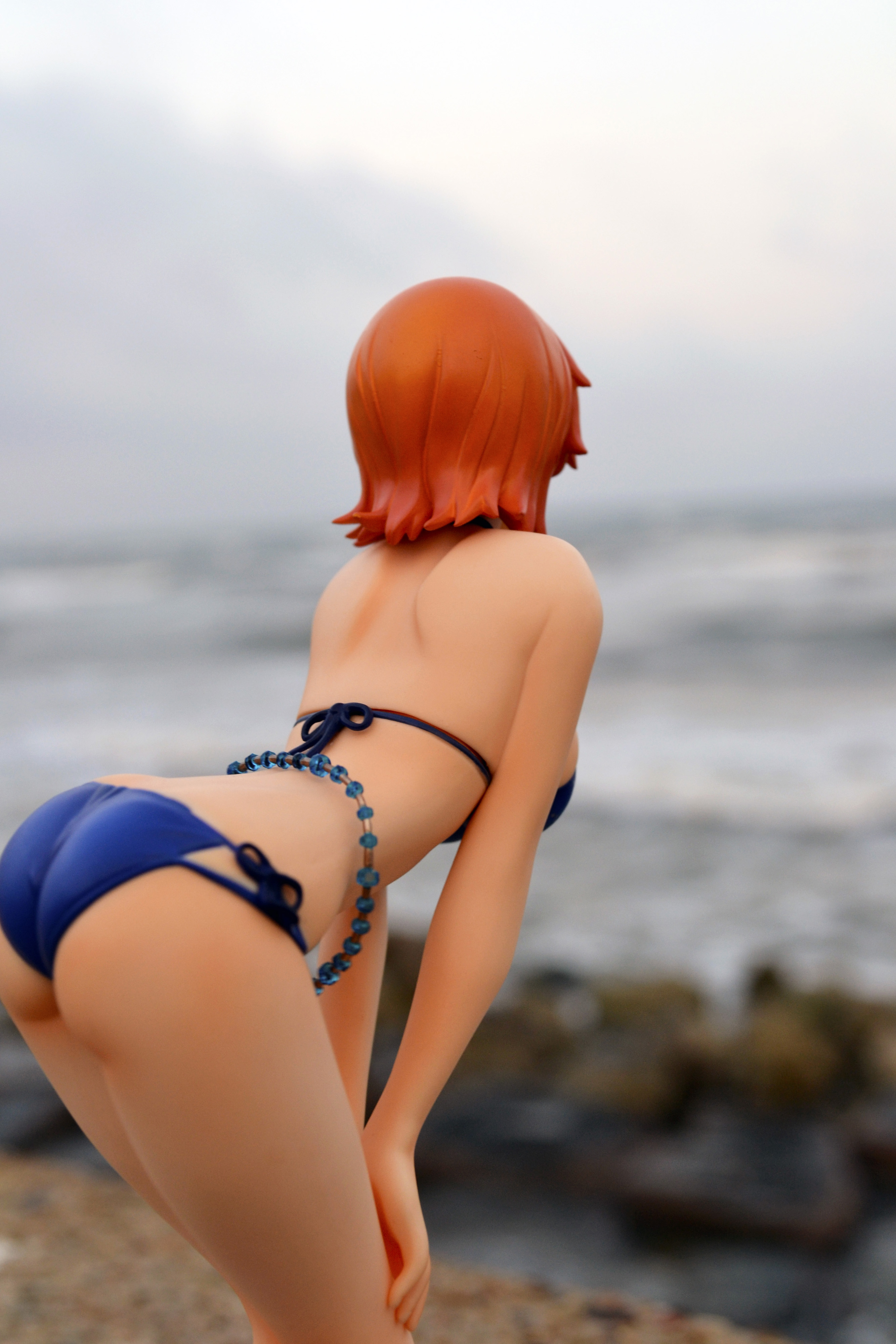 orange_hair bikini leaning_forward beach bare_back buttocks